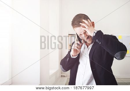Stressed businessman shout making call with mobile phone near window in modern office. Annoyed, frustrated man has unpleasant conversation, show negative emotion. Place for copy space