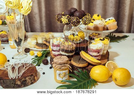 Chocolate Cake Pops, Desserts In Glasses And Biscuits On Wedding Candy Bar. Holiday Candy Bar In Yel