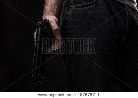 Killer with gun on black background at the studio. The man is holding a gun in his hand. Close-up. Bandit and thief