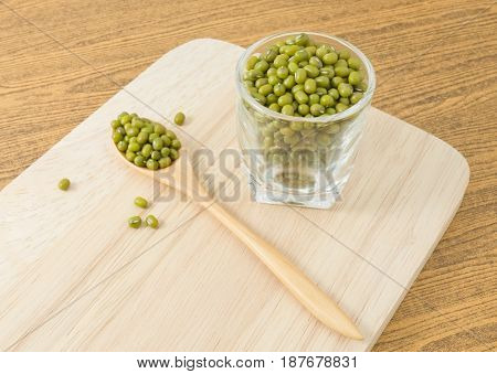 Cuisine and Food Raw and Uncooked Mung Dried Beans in Wooden Spoon and Tumbler on Wooden Cutting Board.