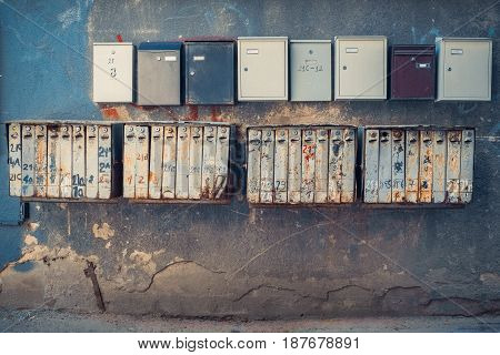 Rows of retro rusty and modern mailboxes on old wall.