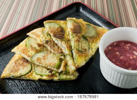 Thai Cuisine and Food Green Eggplant Omelet Served with Spicy Shrimp Paste Dip on Black Tray.