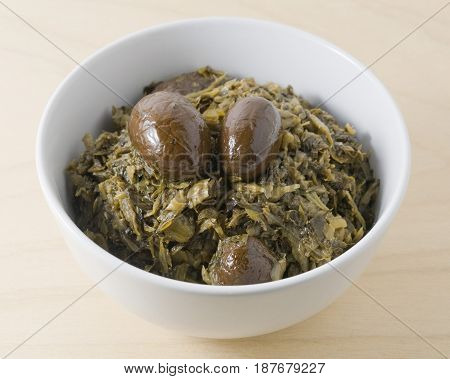 Chinese Traditional Food A Bowl of Chopped Pickled Green Cabbage with Chinese Olives.