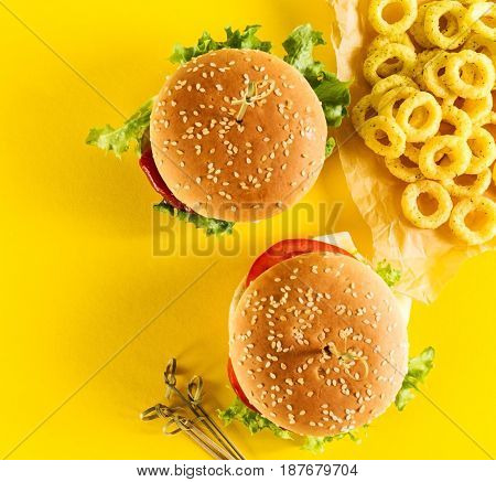 Tasty fresh unhealthy hamburgers with ketchup and vegetables and chips on yellow vibrant bright background. Top View with Copy Space.