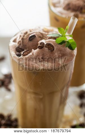 Tasty cold refreshing drink with coffee milk chocolate ice cream and ice in glass on ice background. Closeup.