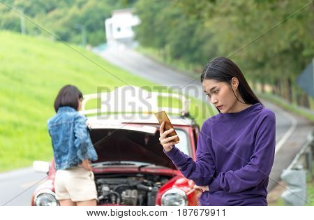 Two young woman using mobile phone while looking at broken down car on street