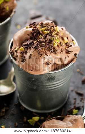 Tasty appetizing creamy chocolate ice cream with pistachios in small metal cup on dark background. Closeup.