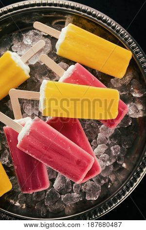 Tasty cold fresh appetizing ice cream on stick on ice cubes on dark background. Closeup.