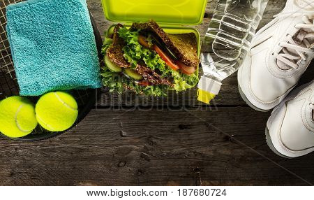 Healthy Life Sport Concept. Sneakers with Lunch Box Towel and Bottle of Water on Wooden Background. Copy Space.