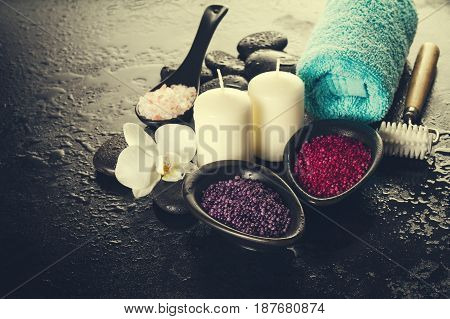 Beautiful Spa Set Spa Products with Essential Oils Soap Towel Spa Sea Salt on Dark Wet Background. Horizontal with Copy Space.
