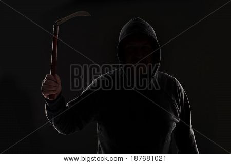 Criminal in dark clothes and balaclava with scythe. On black background at the studio. Bandit and thief