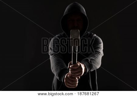 Criminal in dark clothes and balaclava with hammer. On black background at the studio. Bandit and thief