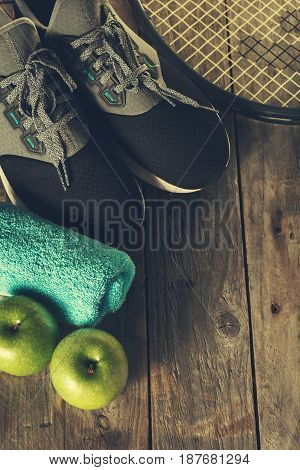 Healthy Life Sport Concept. Sneakers with Apples Towel and Bottle of Water on Wooden Background. Copy Space.