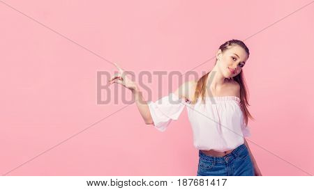 Copy space for advertisement. Colorful portrait of happy smiling young woman pointing away against pink wall.