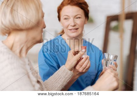 Attentive assistant. Responsible dedicated elderly woman taking the pills and a glass of water the nurse serving her while fulfilling daily routine of doctors prescriptions