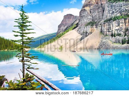 Beautiful Landscape With Rocky Mountains And Tourists Canoeing On Azure Mountain Lake, Alberta, Cana