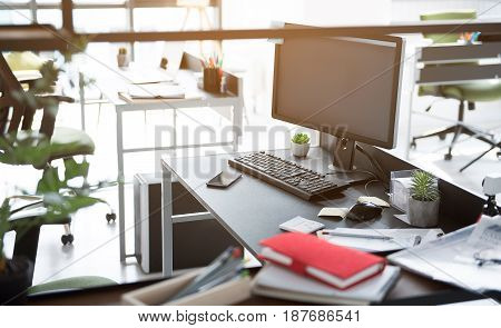 Computer is on table full of different notebooks and documents. Workplace in big office. Nobody