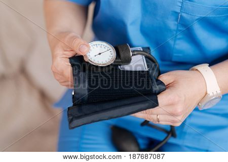 Professional tools. Hardworking neat diligent nurse wanting using some medical equipment for reading patients blood pressure and checking his overall health condition
