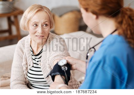 A little check. Relaxed beautiful mature woman sitting on a bed and undergoing medical examination while the nurse using special device for measurements