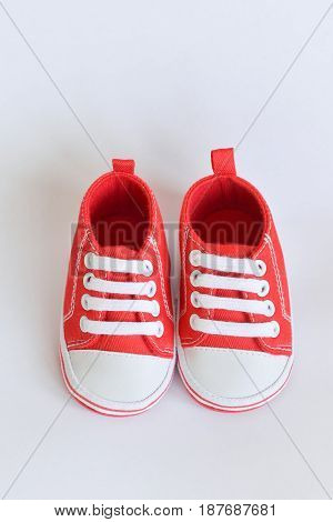 Red sneakers Baby shoes for newborns on isolated background