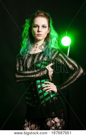 Sensual Woman in cosplay corset posing in studio with a green light from behind. Studio photo. Fashion and cosplay