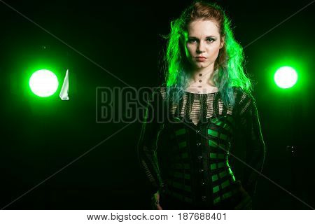 Attractive Woman in cosplay corset posing in studio with a green light from behind. Studio photo. Fashion and cosplay