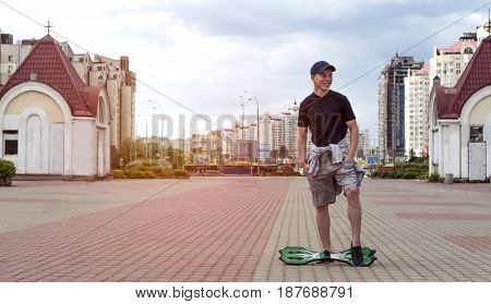 Young man with a skateboard on the street of a big city