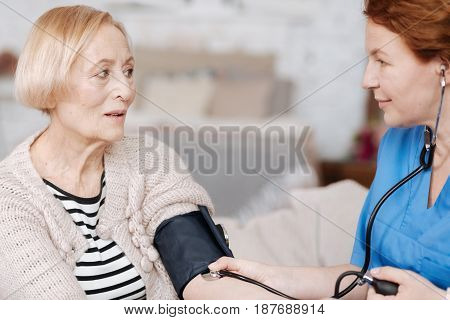 Regular testing at home. Neat graceful medical worker paying her patient a visit for conducting an examination and take care of an elderly lady
