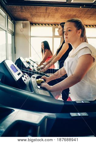 Fitness girl burning calories on the treadmill. Beautiful young cheerful girl in sportswear exercising on treadmill at gym with other girls