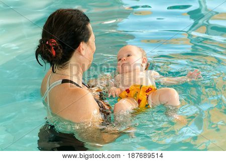 Adorable Baby Enjoying Swimming In A Pool With His Mother