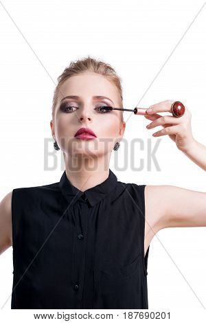 Beautiful young woman applying mascara with brush, studio beauty portrait. Applying cosmetic, eyes makeup. Dark evening make-up and jewelry in beauty concept. Fashion photo.