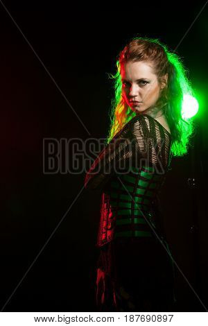 Attractive cosplay model in corset in studio photo with a red and green light from behind. Cosplay and subculture
