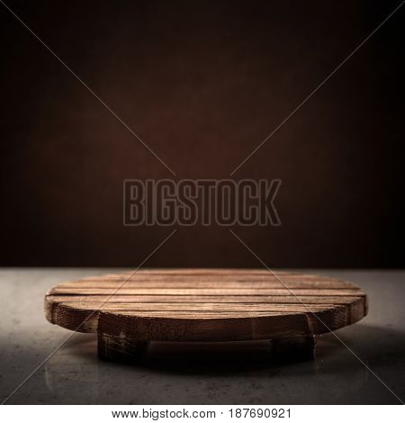 Wooden round stand for the bitterness of food on a dark background, place for inscription, cover