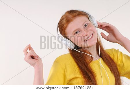 Beautiful young woman with headphones relaxing by listening music. Chill out and leisure concept. Natural redhaired teenage girl