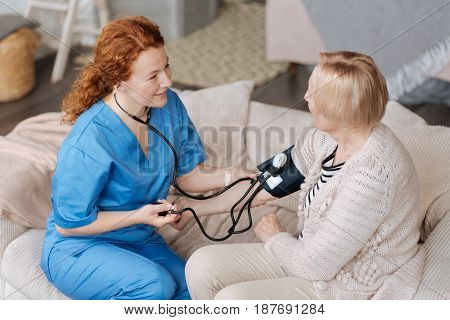 Delicate consultation. Prominent persistent energetic woman visiting elderly patient and reading her blood pressure employing professional tonometer