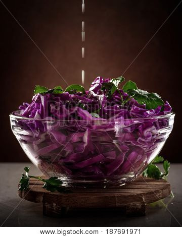 olive oil in a thin stream pour into Salad of red cabbage in glass transparent bowl on dark background