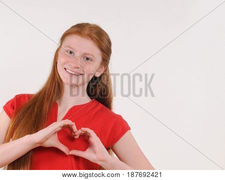 Portrait of a young red hair girl showing heart shape with hands on grey background. Happy smiling lifestyle people concept. Human emotions.