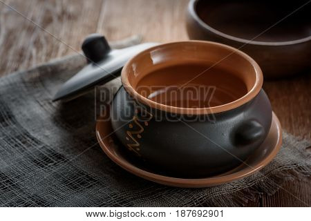 Clay pot for baking with lid on a linen napkin on wooden background