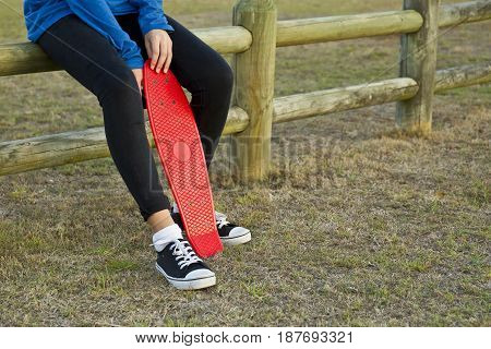 Young woman sitting on a wooden fence with her skate board between her legs