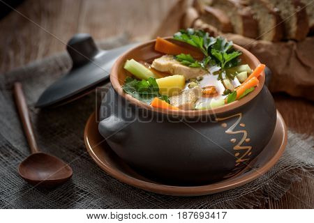 soup in the pot, bread, wooden spoon on the table closeup
