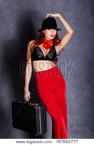 woman in red pants and black hat with big boobs hold retro suitcase.