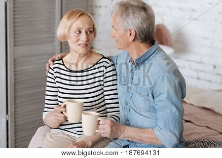 Gentle hug. Charming lovely sweet family sharing a moment of unity while sitting on a bed and enjoying warm drinks