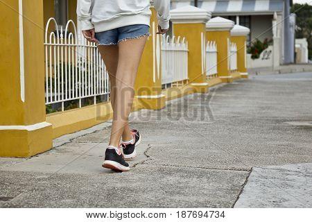 young woman wearing shorts a training shoes walking along concrete a path