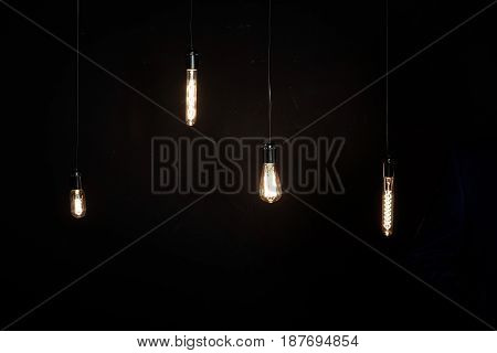 Bright glowing light bulbs of different shapes on the dark background