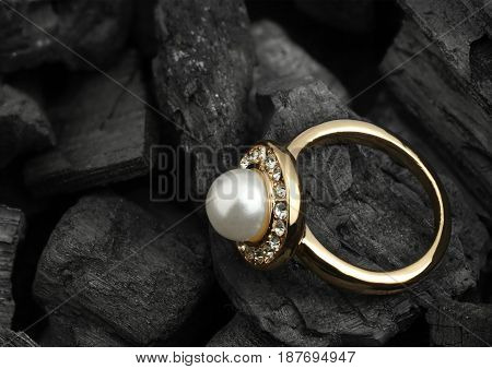 jewelry ring with diamond and pearl on black coal background