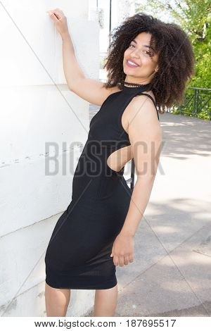 Cheerful Thin Woman In A Black Dress With A Cleavage In The Back