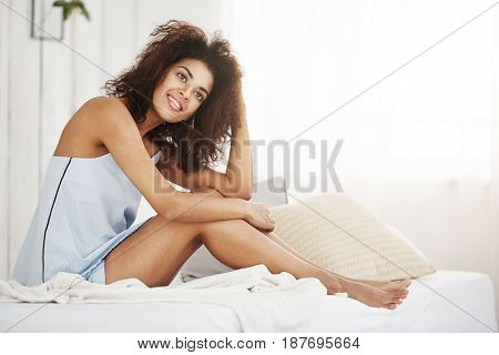 Young dreamy tender african girl in sleepwear sitting on bed in morning smiling thinking. Copy space.