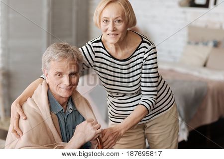 In sickness and health. Perfect sweet glorious wife sharing a nice moment while bringing her husband a blanket and helping him recovering