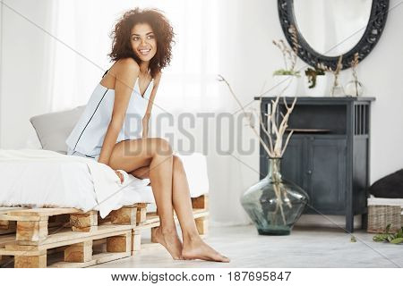 Young dreamy tender african girl in sleepwear sitting on bed in morning smiling thinking.