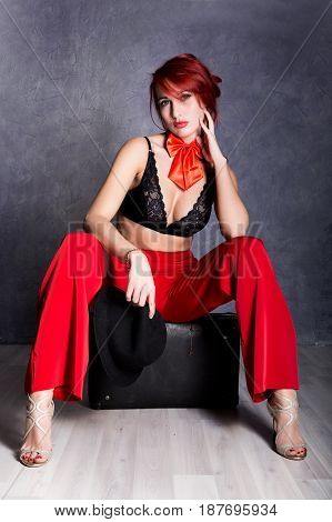 woman in red pants and black hat with big boobs sits on a retro suitcase.